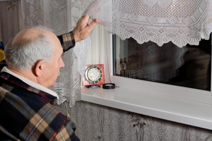 elderly-man-peering-out-window-dark-night-as-waits-expected-arrival-clock-front-him-34192410