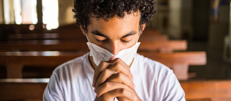 Jovem reza em igreja utilizando máscara de proteção.